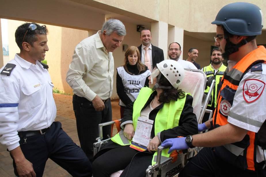 ראש העיר צביקה גנדלמן מרגיע פצועה שפונתה מזירת הטיל