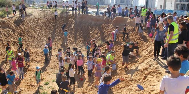 יצאו לשטח. ההורים והילדים מפנים חול (צילום: רועי כפיר)