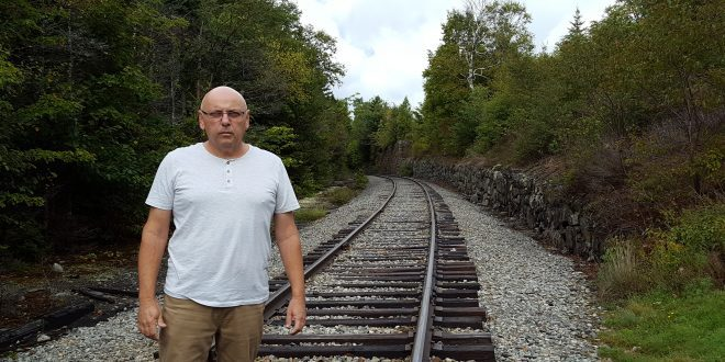 מתי תעצרו גם אצלנו? יהודה ברונר על רקע פסי הרכבת. צילום: פרטי