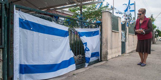 דליה גראו ליד הדגל שהושחת בכניסה לביתה. צילום: דורון גולן