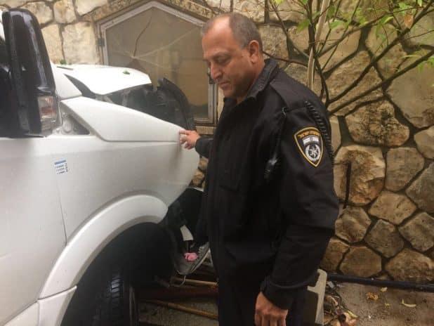 השוטרים בודקים את הרכב שהתנגש בקיר (צילום דוברות המשטרה)
