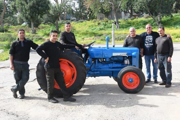 """סמסונוב עם האני ג'ומעה וצוות """"מוסך הגבעה"""", המתמחה בשיפוץ טרקטורים ומכונות חקלאיות (צילום: הילה אייזינגר)"""