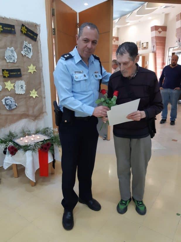 מפקד התחנה משה ויצמן מעניק תעודת הוקרה לניצול שואה