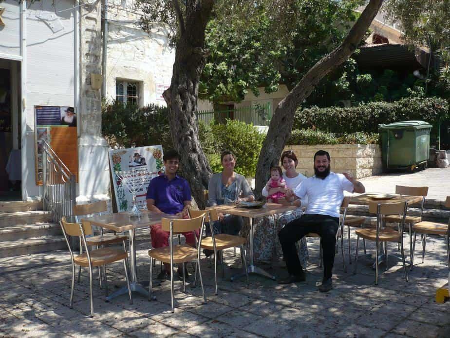 משה ואשתו שרה עם בתם התינוקת בפתח בית הקפה, עם אלכסנדה ורפאל - שני עולים צעירים מצרפת
