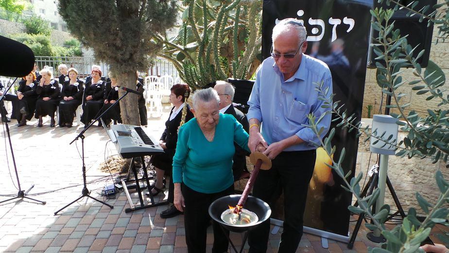 השר אורי אריאל מדליק משואה יחד עם ניצולי השואה