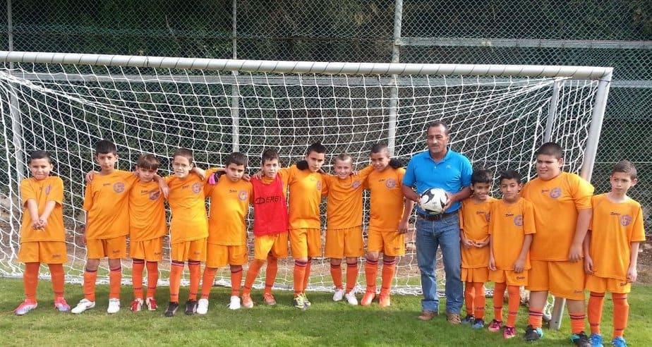 נעים להכיר. קבוצת הכדורגל של מעלה יוסף עם המאמן יוסי עזור (צילום: איתי קדם)