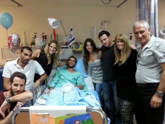 מקיפים באהבה. משפחת אלעד סביב מיטת הבן הפצוע, יובל צילום: עצמי