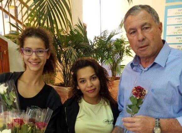 """המורה, רוצה פרח? המנהל ד""""ר דודי גושן והתלמידות (צילום: עיריית חיפה)"""