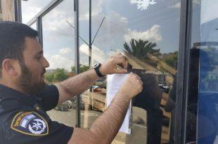 שוטר מדביק את צו הסגירה למועדון (צילום דוברות המשטרה)