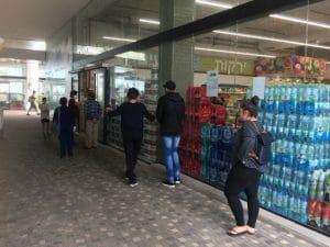 תושבים שומרם מרחק בתור בכניסה לסופר סיטי, נווה פרדסים, אכיפה נרחבת פרדס חנה (צילום: נירית שפאץ)
